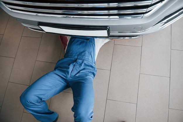 Vista superior. hombre de uniforme azul trabaja con coche roto. realización de reparaciones.