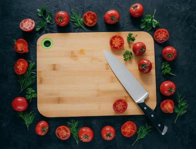 Vista superior horizontal de tomates rojos alrededor de la tabla de cortar de madera.