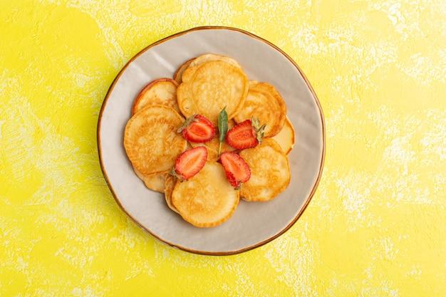 Vista superior horneados deliciosos panqueques dentro de la placa marrón con fresas en rodajas en el escritorio amarillo panqueques comida fruta baya postre dulce
