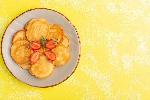Vista superior horneados deliciosos panqueques dentro de la placa marrón con fresas en rodajas en la pared amarilla postre dulce baya de alimentos para panqueques