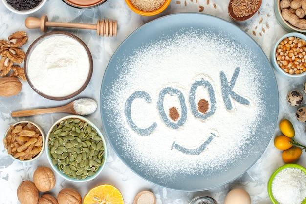 Vista superior de la huella del cocinero en harina en polvo en la placa nueces cuchara de madera tazón de harina cumcuats