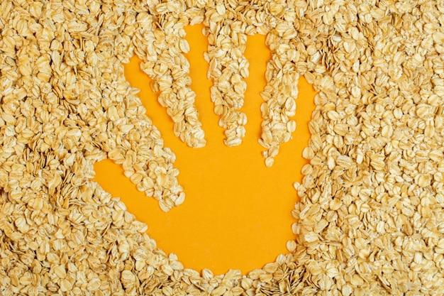 Vista superior de la huella de la mano en copos de avena en amarillo