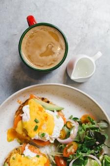 Vista superior del huevo benedict con salmón y aguacate. servido con café caliente y leche.