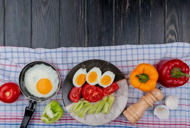 Vista superior del huevo frito con huevos hervidos a la mitad en un plato con rodajas de tomate y rodajas de pimiento sobre un mantel a cuadros sobre un fondo de madera con espacio de copia
