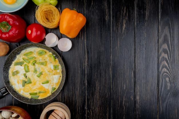 Vista superior del huevo frito en una sartén con cáscaras de huevo con coloridos pimientos sobre un fondo de madera con espacio de copia