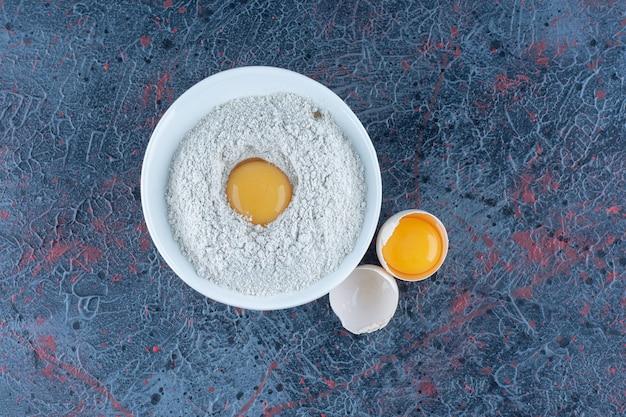 Vista superior del huevo de gallina blanco fresco roto con yema y clara de huevo.