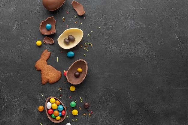 Vista superior del huevo de pascua de chocolate con dulces y galletas en forma de conejito