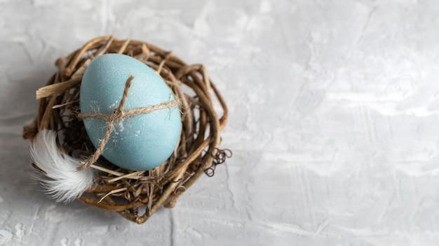 Vista superior del huevo de pascua en nido de pájaro con espacio de copia