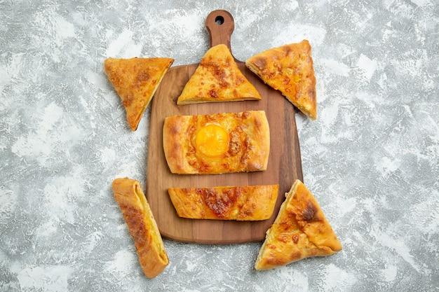 Vista superior del huevo en rodajas hornear deliciosos pasteles con condimentos sobre fondo blanco pastelería hornear masa comida pizza comida