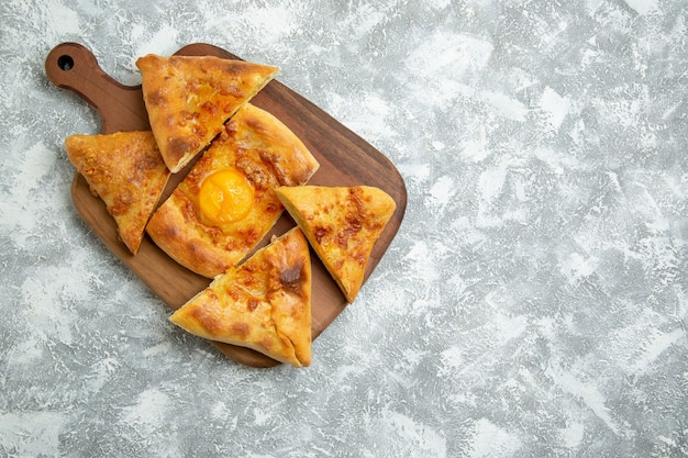 Vista superior de huevo en rodajas pastelería pan horneado sobre piso blanco pastelería horno masa comida comida pan bollo