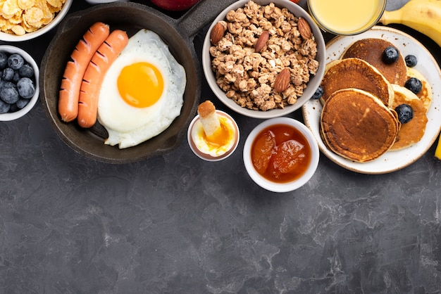 Vista superior de huevo con salchichas y cereales para el desayuno.