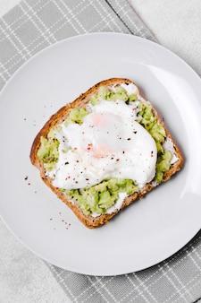 Vista superior de huevo con tostadas de aguacate en placa