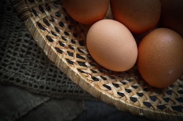 Vista superior de los huevos en una canasta de paja sobre una servilletas de lino natural y un fondo de madera rústica