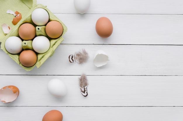 Vista superior de huevos en cartón para pascua con plumas y espacio de copia