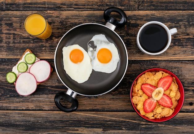 Vista superior de huevos fritos con tostadas, copos de maíz y bebidas en la superficie de madera oscura horizontal