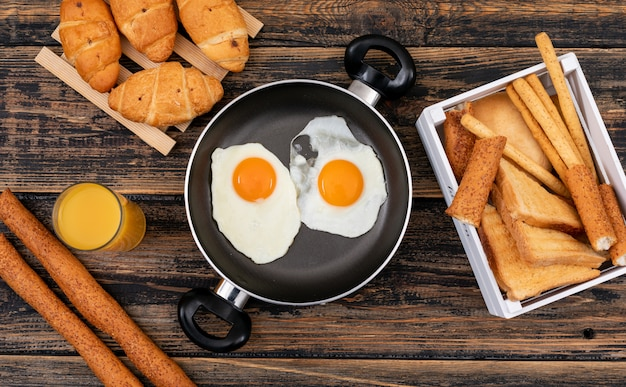 Vista superior de huevos fritos con tostadas, cruasanes y jugo en superficie de madera oscura horizontal
