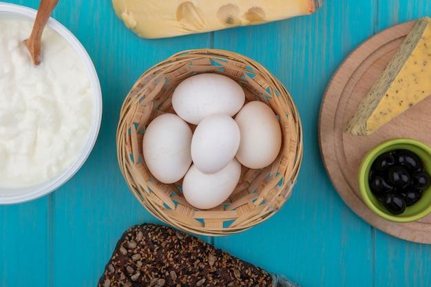 Vista superior de huevos de gallina en una canasta de queso con pan negro y yogur en un recipiente sobre un fondo turquesa