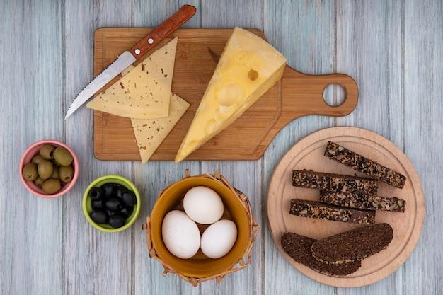 Vista superior de los huevos de gallina en una canasta con rebanadas de pan negro sobre un soporte con quesos sobre una tabla de cortar y un cuchillo sobre un fondo gris