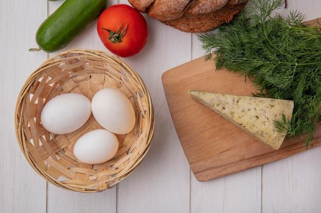 Vista superior de los huevos de gallina en una canasta con tomate pepino y una hogaza de pan negro con queso y eneldo sobre fondo blanco.