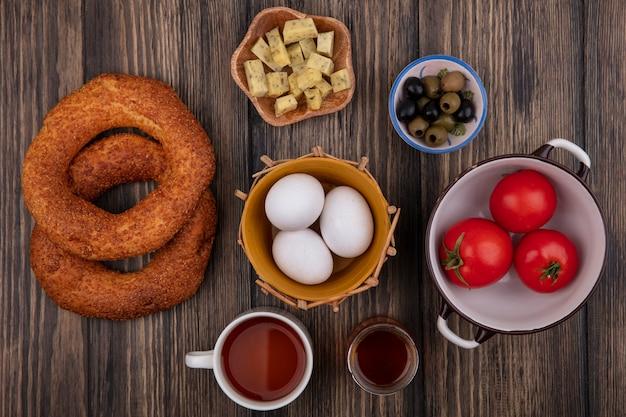 Vista superior de huevos orgánicos en un balde con queso en un cuenco de madera con tomates en un cuenco y con una taza de té sobre un fondo de madera