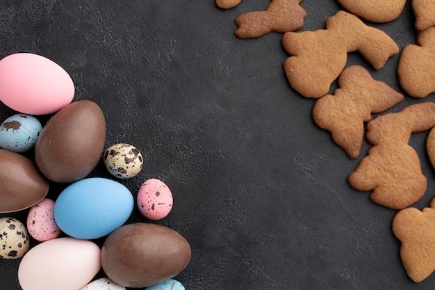 Vista superior de huevos de pascua de chocolate con galletas en forma de conejito