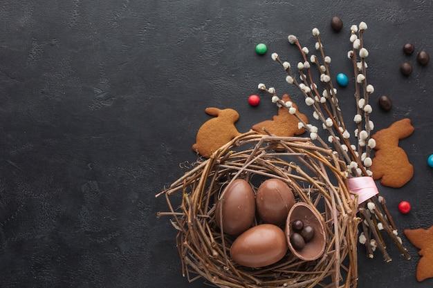 Vista superior de los huevos de pascua de chocolate en el nido con dulces y espacio de copia