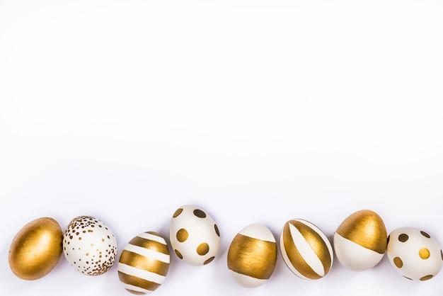 Vista superior de los huevos de pascua coloreados con pintura dorada en diferentes patrones.