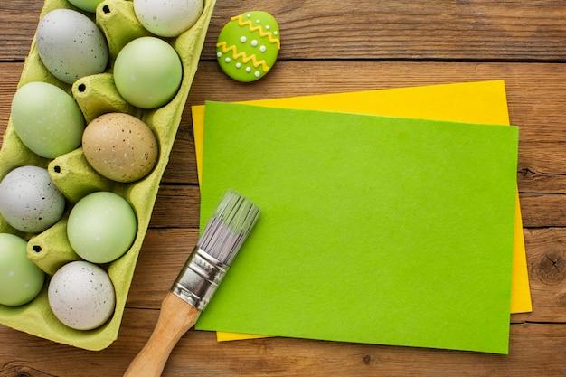 Vista superior de huevos de pascua de colores en cartón con pincel y papeles