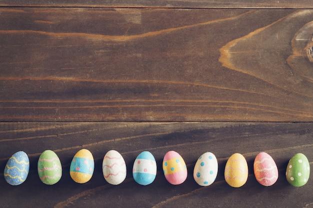 Vista superior de los huevos de pascua en el fondo de madera rústico con espacio de copia