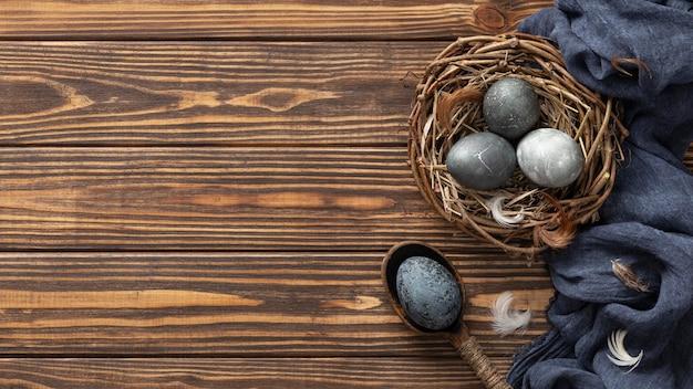 Vista superior de huevos de pascua en nido de pájaro con espacio textil y copia