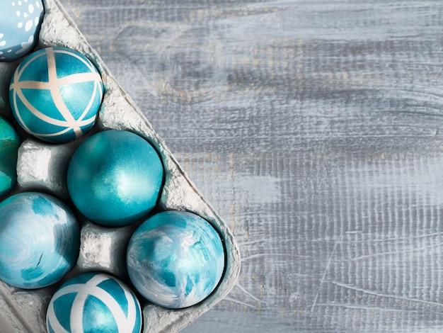 Vista superior de huevos de pascua pintados en cartón con espacio de copia