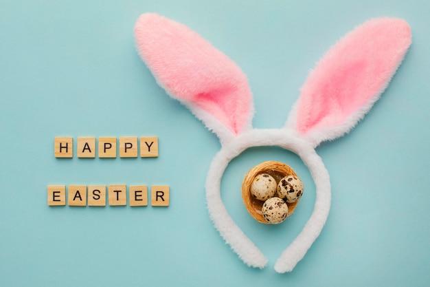 Vista superior de huevos de pascua con saludo y orejas de conejo
