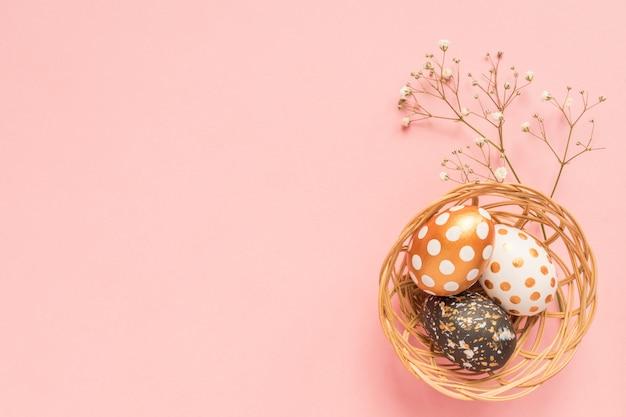 Vista superior de huevos pintados de madera en colores oro, negro y rosa en cesta de mimbre con rama de gypsophila sobre fondo rosa.