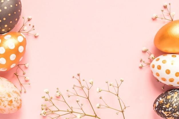 Vista superior de huevos pintados de madera en colores oro, negro y rosa con rama de gypsophila sobre fondo rosa.