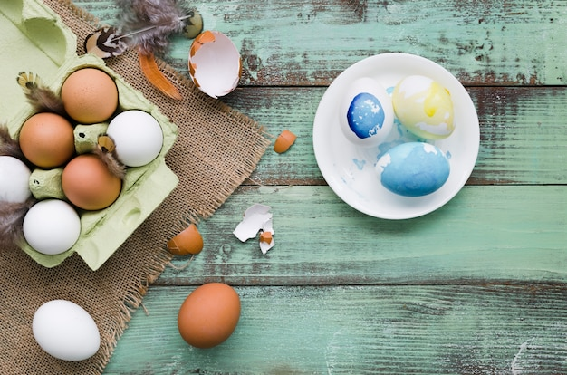 Vista superior de huevos pintados en un plato para pascua con plumas