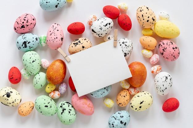 Vista superior huevos pintados con tarjeta de papel