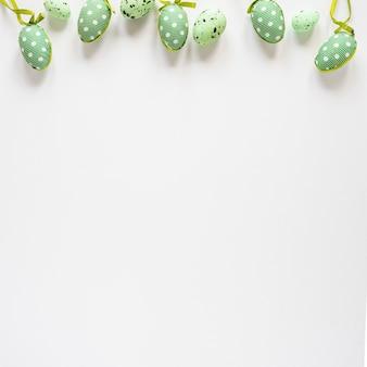 Vista superior de huevos pintados de verde en la mesa