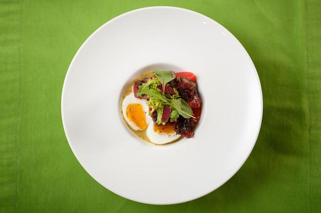 Vista superior de los huevos del plato con la reunión y la ensalada en la placa
