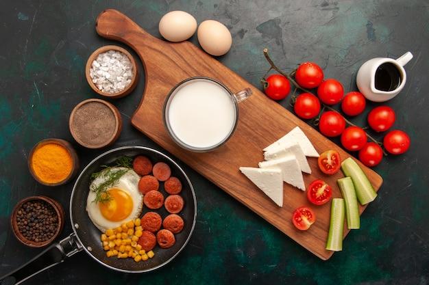 Vista superior de huevos revueltos con salchichas y con condimentos de tomates frescos sobre fondo oscuro