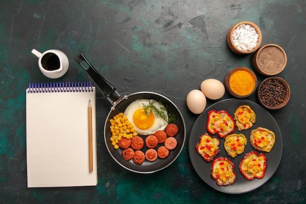 Vista superior de huevos revueltos con salchichas y diferentes condimentos sobre fondo oscuro