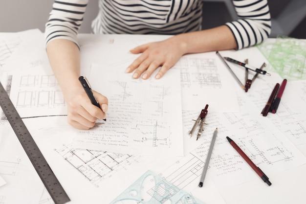 Vista superior del ingeniero independiente joven y guapo con ropa formal a rayas que trabaja en una cómoda mesa bif, tomando notas cerca de planos para arreglarlos más tarde.