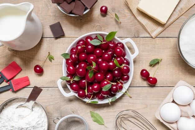 Vista superior de ingredientes crudos para cocinar pastel de cerezas sobre fondo de madera