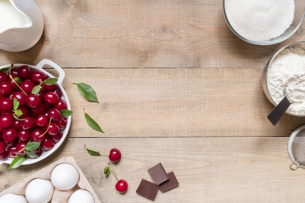 Vista superior de ingredientes crudos para cocinar tarta de cerezas sobre fondo de madera con espacio de copia