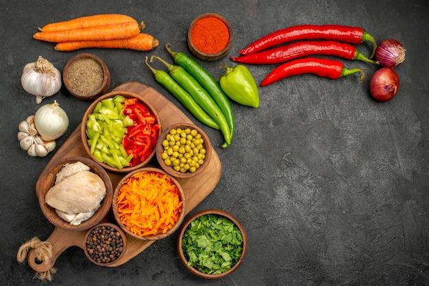 Vista superior de ingredientes de ensalada fresca con condimentos en color de comida de comida de ensalada de mesa oscura