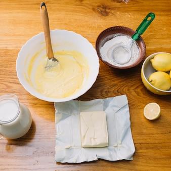 Vista superior de ingredientes frescos para hacer pastel en mesa de madera