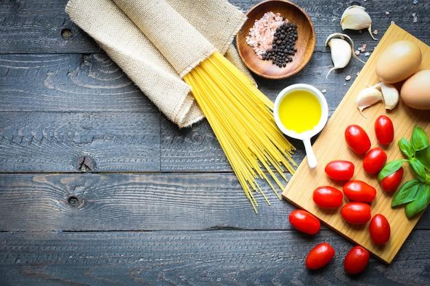 Vista superior de ingredientes italianos para tomate y espagueti basilico.