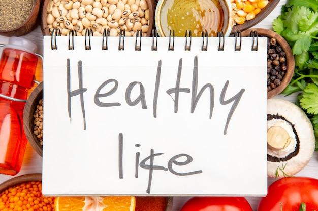 Vista superior de una inscripción de vida sana en un cuaderno de espiral sobre verduras frescas, granos de maíz de limón, miel de botella de aceite de limón caído sobre fondo blanco