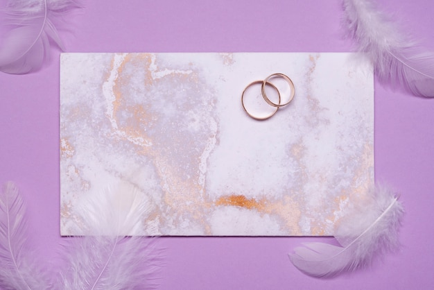 Vista superior invitación de boda y anillos de compromiso