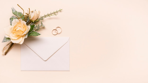 Vista superior invitación de boda con anillos de compromiso