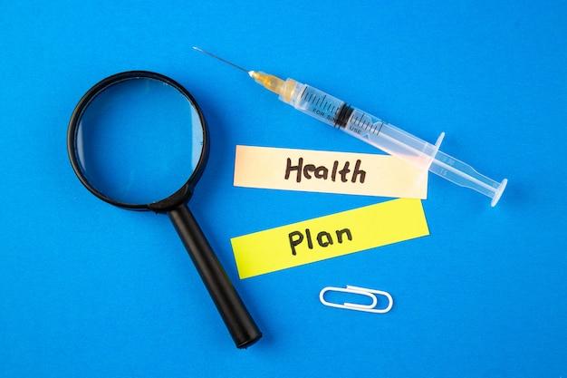 Vista superior de inyección de antivirus con notas y magnfier sobre fondo azul laboratorio de pandemia de virus hospitalario covid- cura medicina de medicamentos de salud